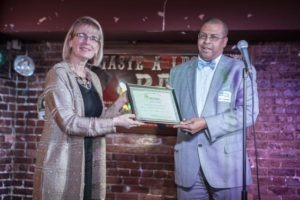 Janine Finnell, Founder and Clean Energy Ambassador, Leaders in Energy, presents the Baby Boomer Generation Award for Robert L. Wallace to Harry Holt, VP of Operations, Bithgroup Technologies. Photo Credit: Augustine Cruz, augie.cruz@gmail.com.